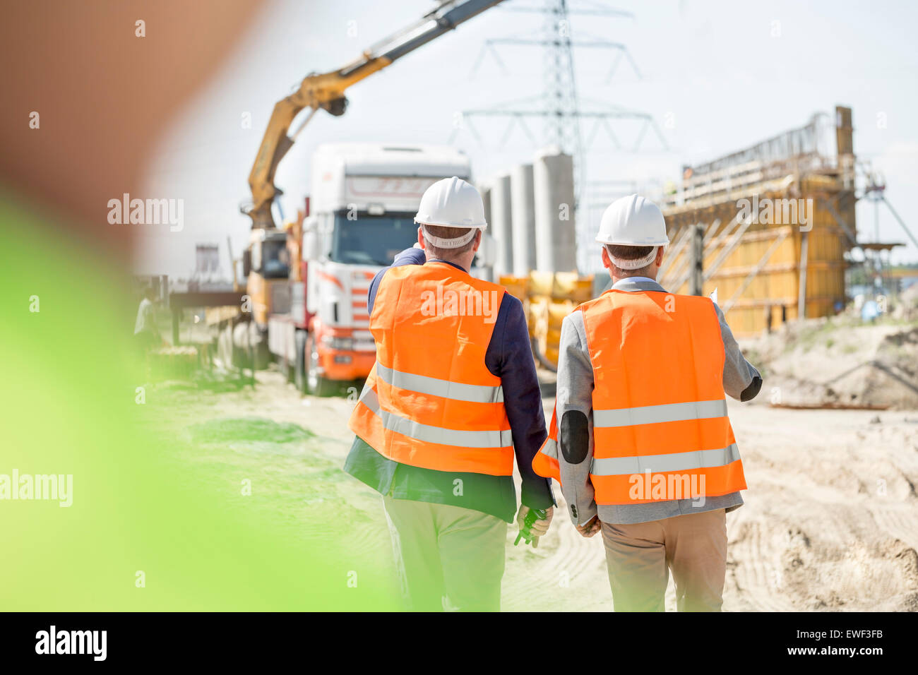 Rear view of supervisors walking at construction site - Stock Image