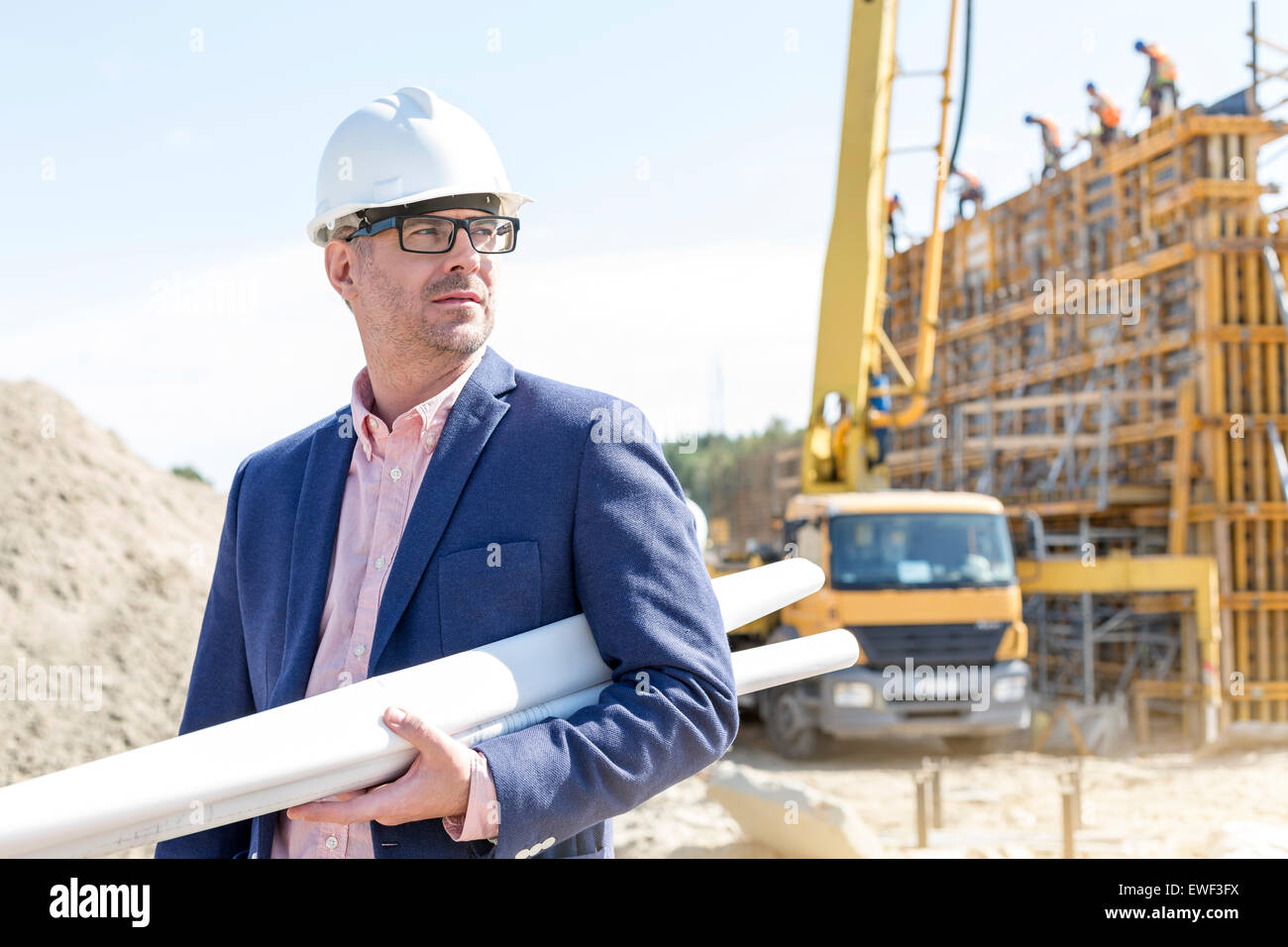 Confident architect holding rolled up blueprints at construction site - Stock Image
