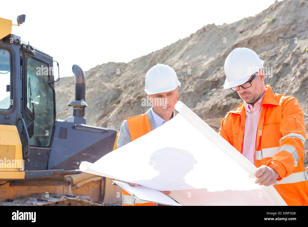 Engineers analyzing blueprint at construction site - Stock Image