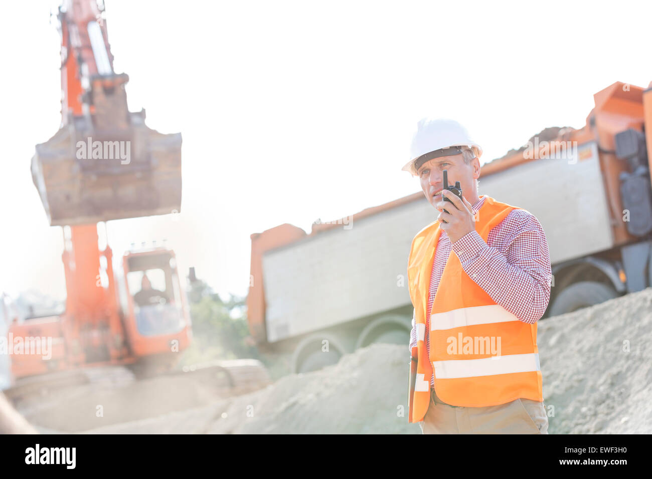 Architect using walkie-talkie while working at construction site - Stock Image