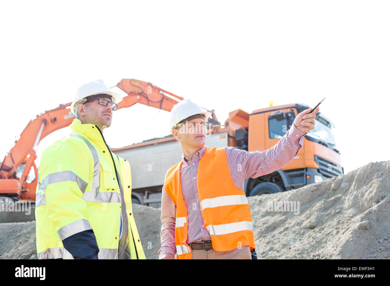 Engineer showing something to colleague while discussing at construction site against clear sky - Stock Image
