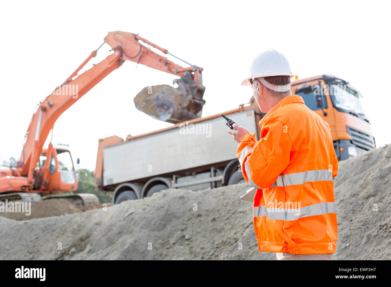Side view of architect using walkie-talkie while working at construction site - Stock Image