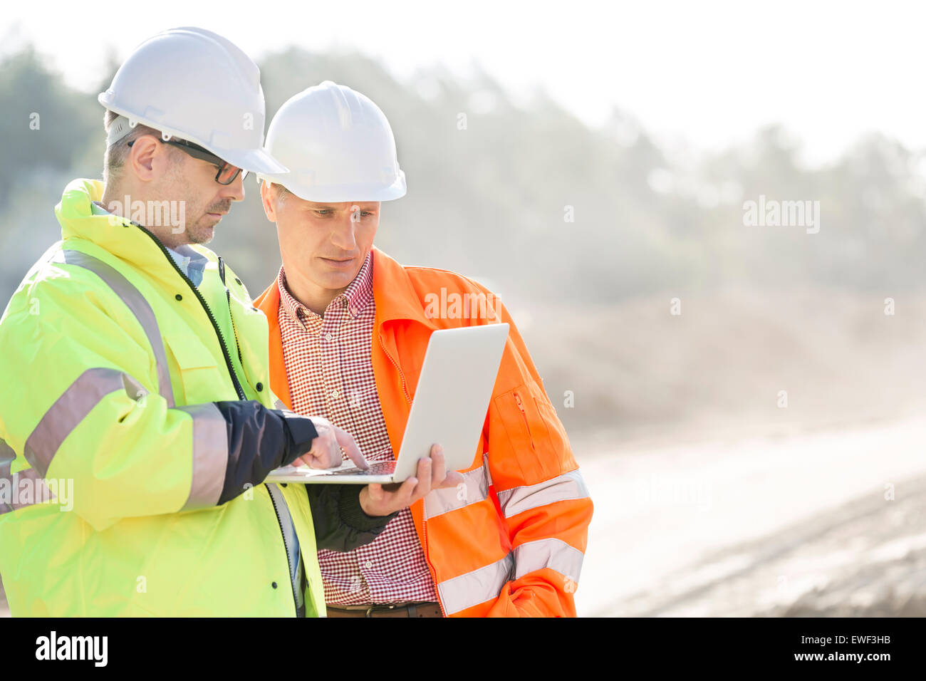 Supervisors using laptop at construction site - Stock Image
