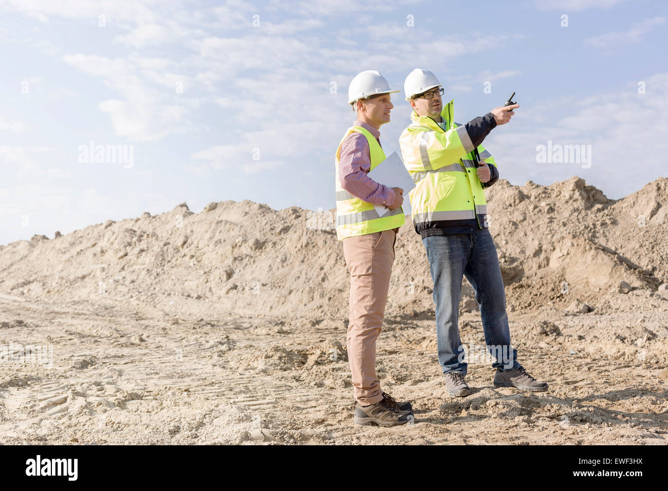 Supervisor examining construction site against sky - Stock Image