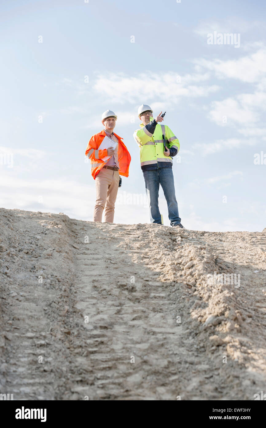Low angle view of architect showing something to colleague at construction site against sky - Stock Image