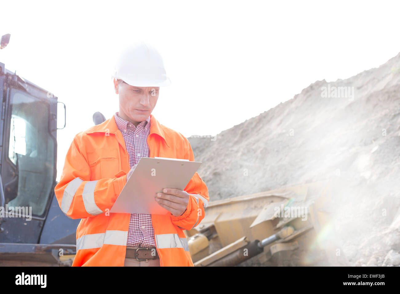 Engineer reading clipboard at construction site - Stock Image