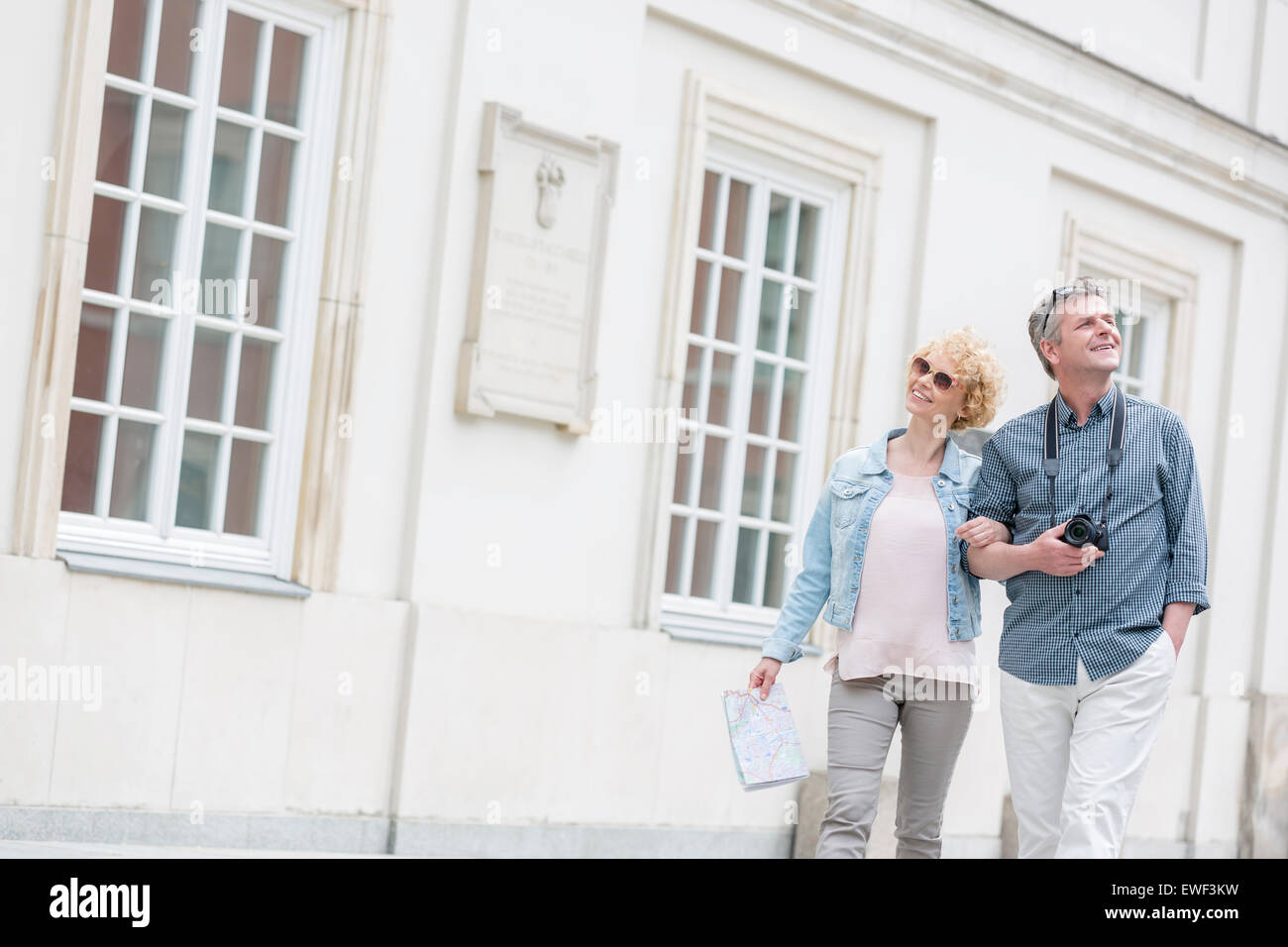 Happy middle-aged tourist couple walking arm in arm by building - Stock Image