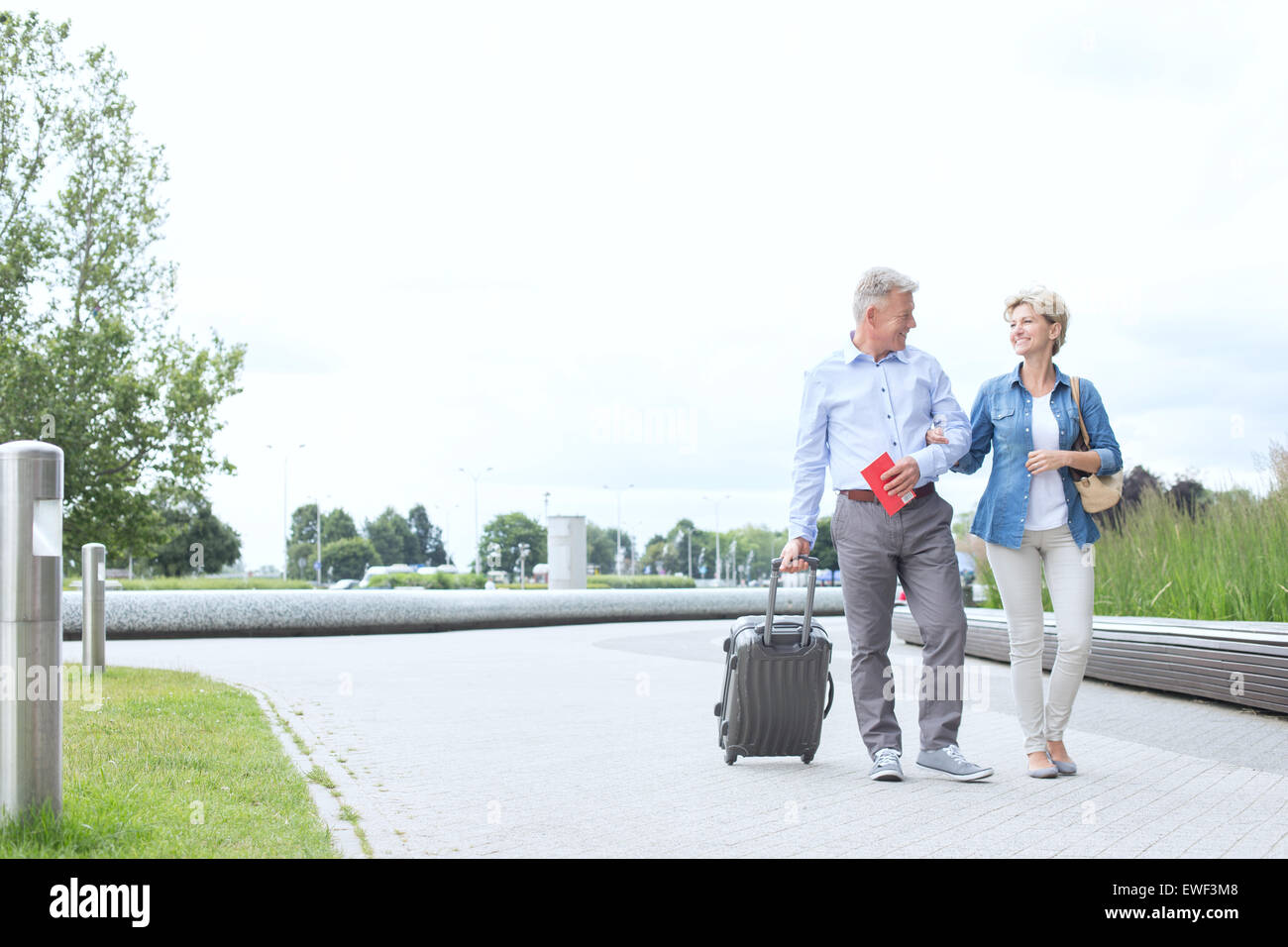 Middle-aged couple with luggage walking on footpath against clear sky - Stock Image