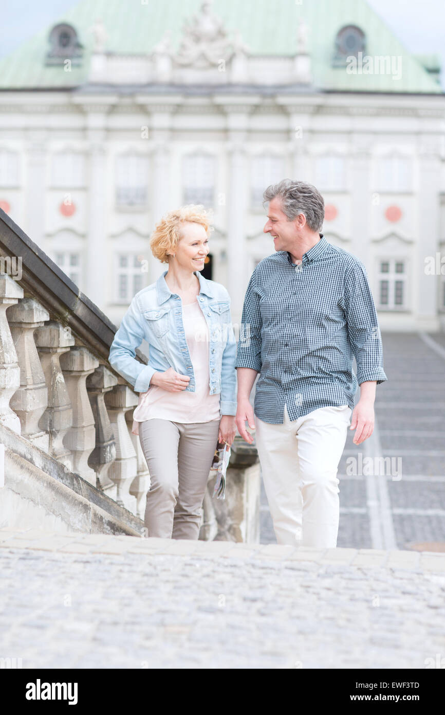 Happy middle-aged couple looking at each other while climbing steps Stock Photo