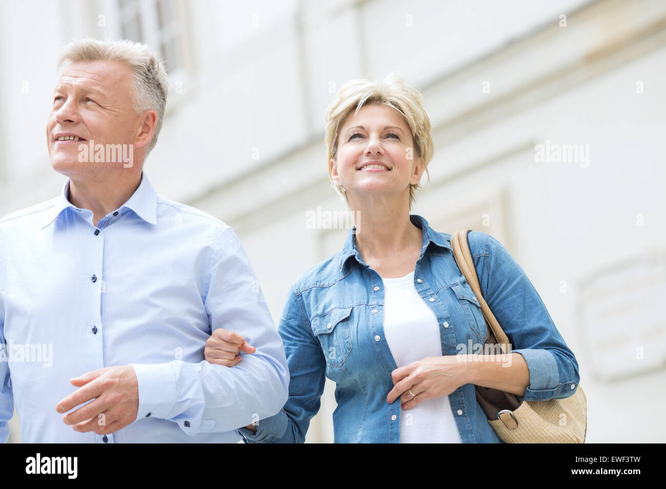 Smiling middle-aged couple standing with arm in arm outdoors - Stock Image