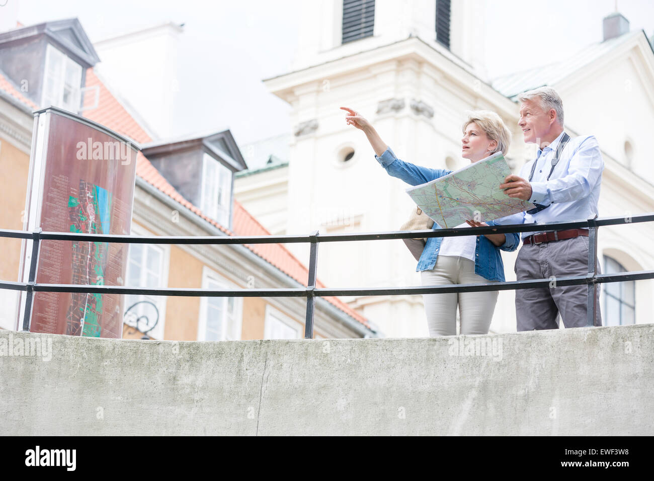 Middle-aged woman showing something to man while reading map by railing - Stock Image