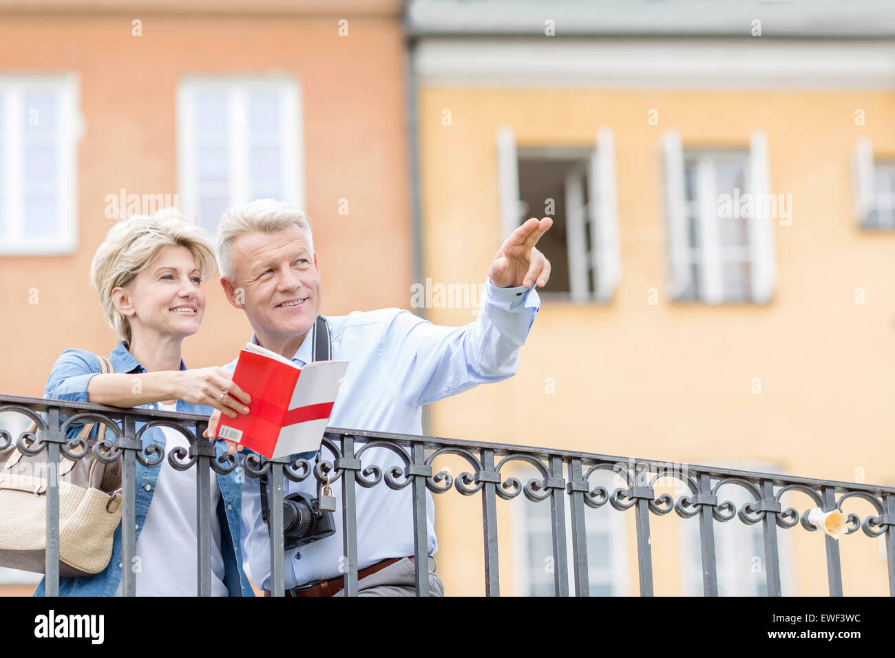 Happy man showing something to woman with guidebook in city - Stock Image