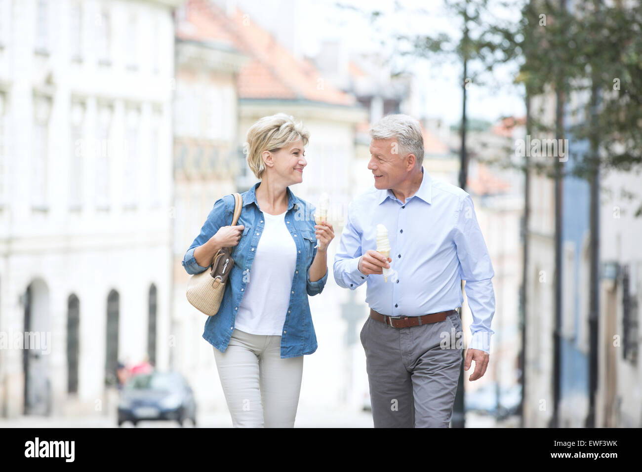 Happy middle-aged couple looking at each other while holding ice cream cones in city - Stock Image