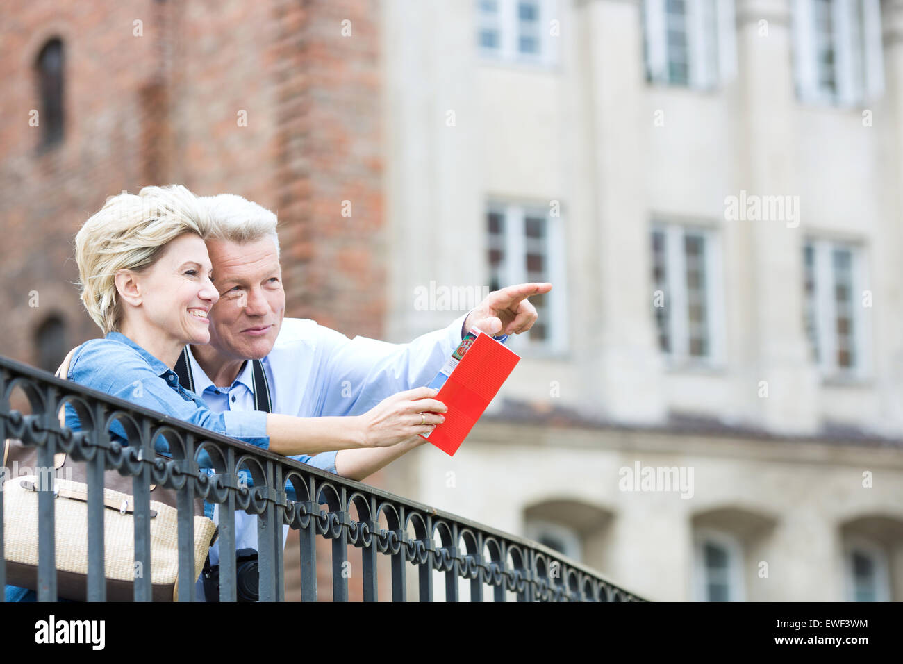 Smiling middle-aged man showing something to woman with guidebook in city - Stock Image