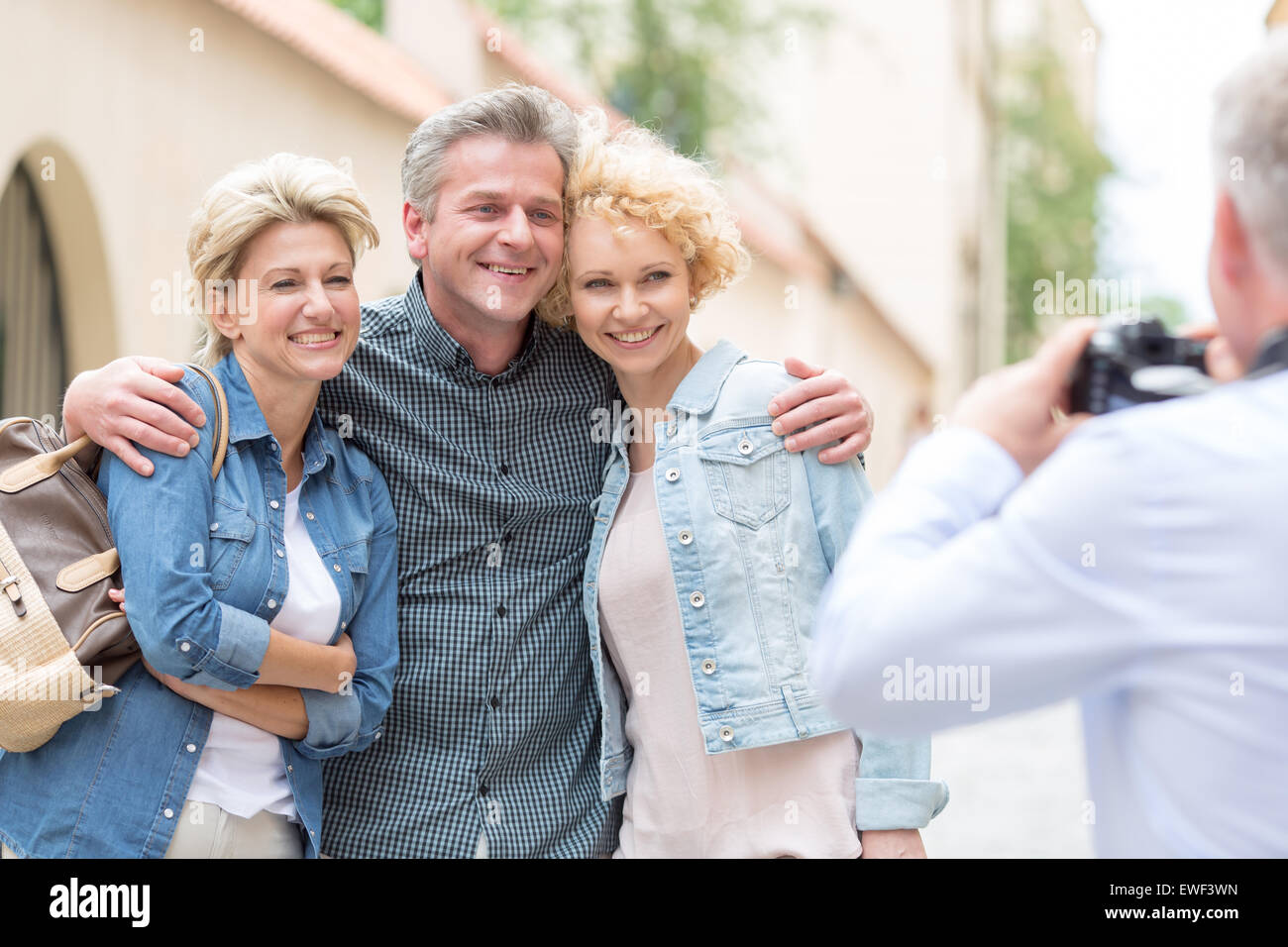 Rear view of man photographing male and female friends in city - Stock Image