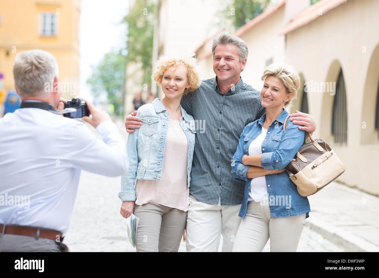 Rear view of man photographing friends in city - Stock Image