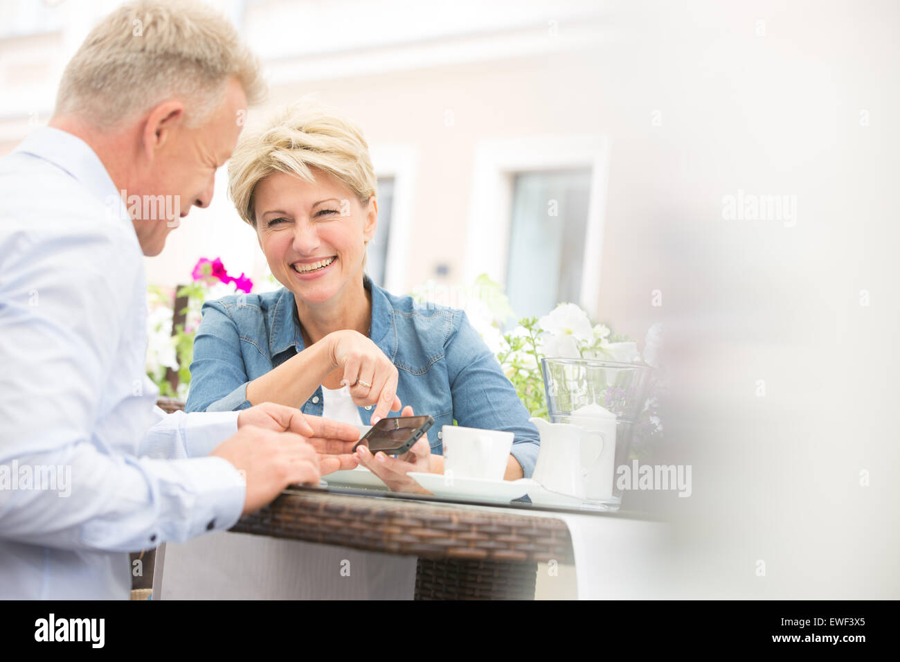 Happy middle-aged couple using mobile phone at sidewalk cafe - Stock Image