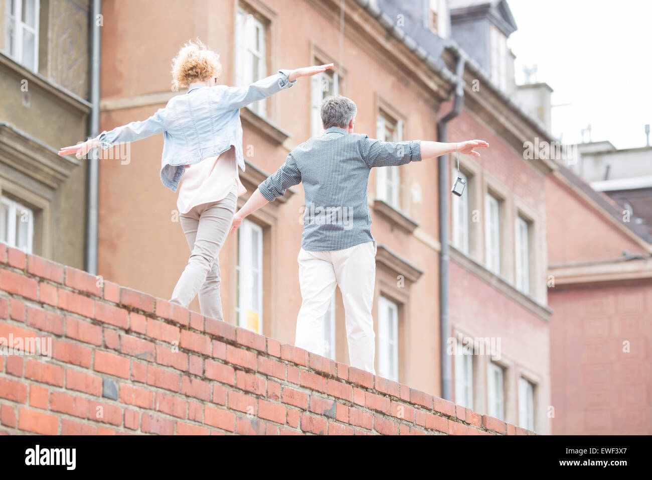 Rear view of middle-aged couple with arms outstretched walking on brick wall - Stock Image