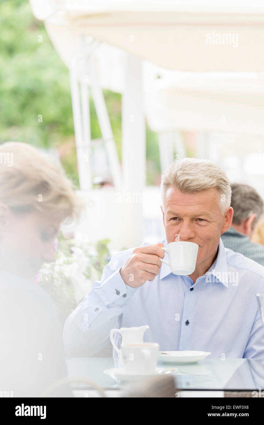 Middle-aged man looking at woman while having coffee at sidewalk cafe - Stock Image