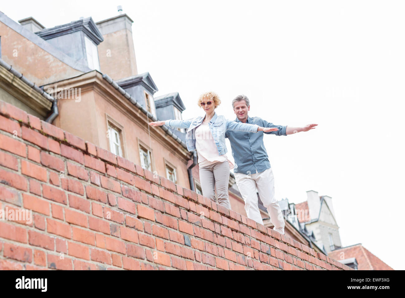 Low angle view of middle-aged couple with arms outstretched walking on brick wall against clear sky - Stock Image