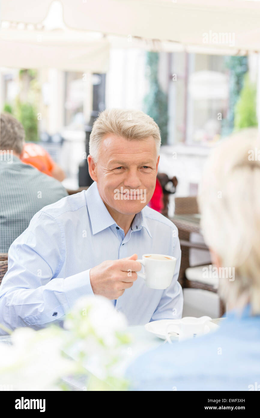 Smiling middle-aged man having coffee with woman at sidewalk cafe - Stock Image