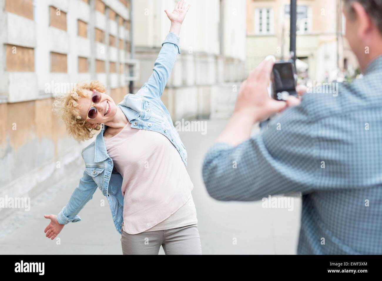 Man photographing playful woman standing with arms outstretched on city street - Stock Image