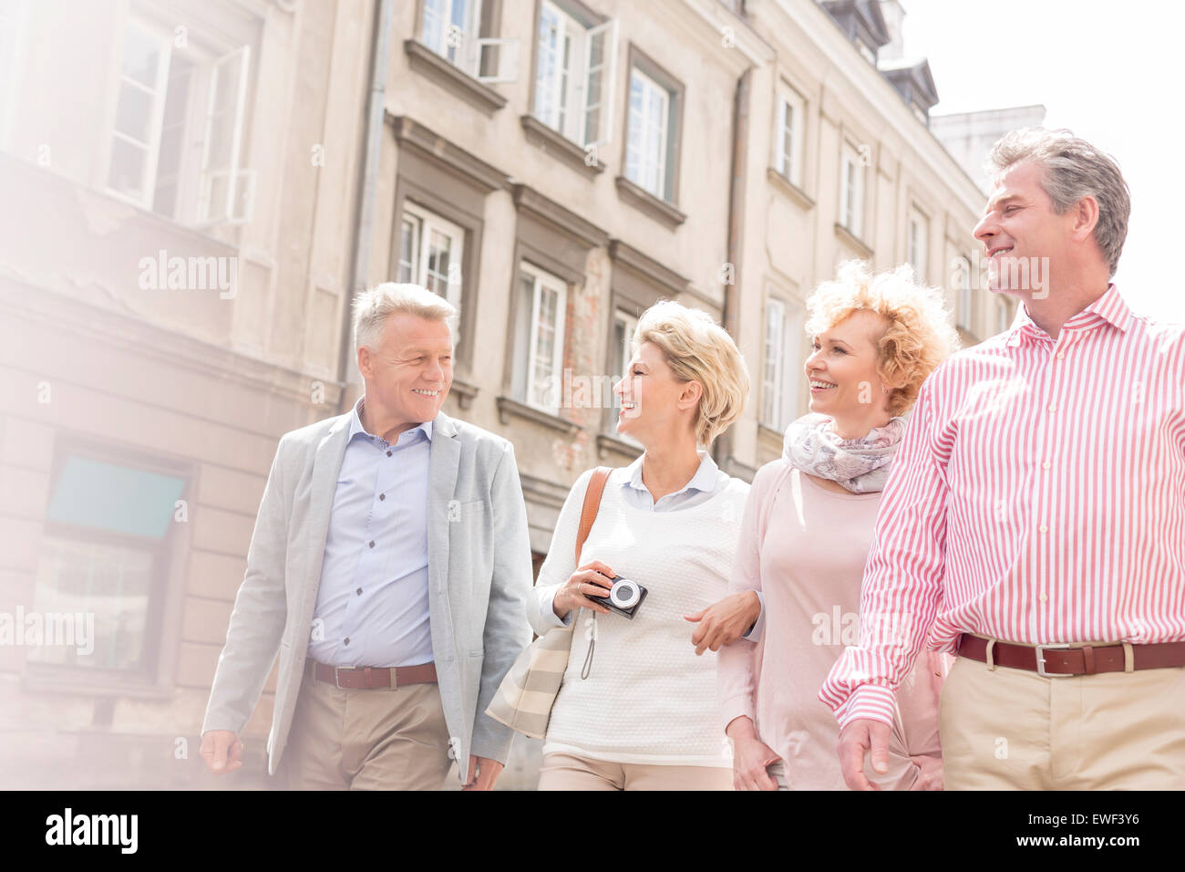 Happy friends talking while walking in city - Stock Image