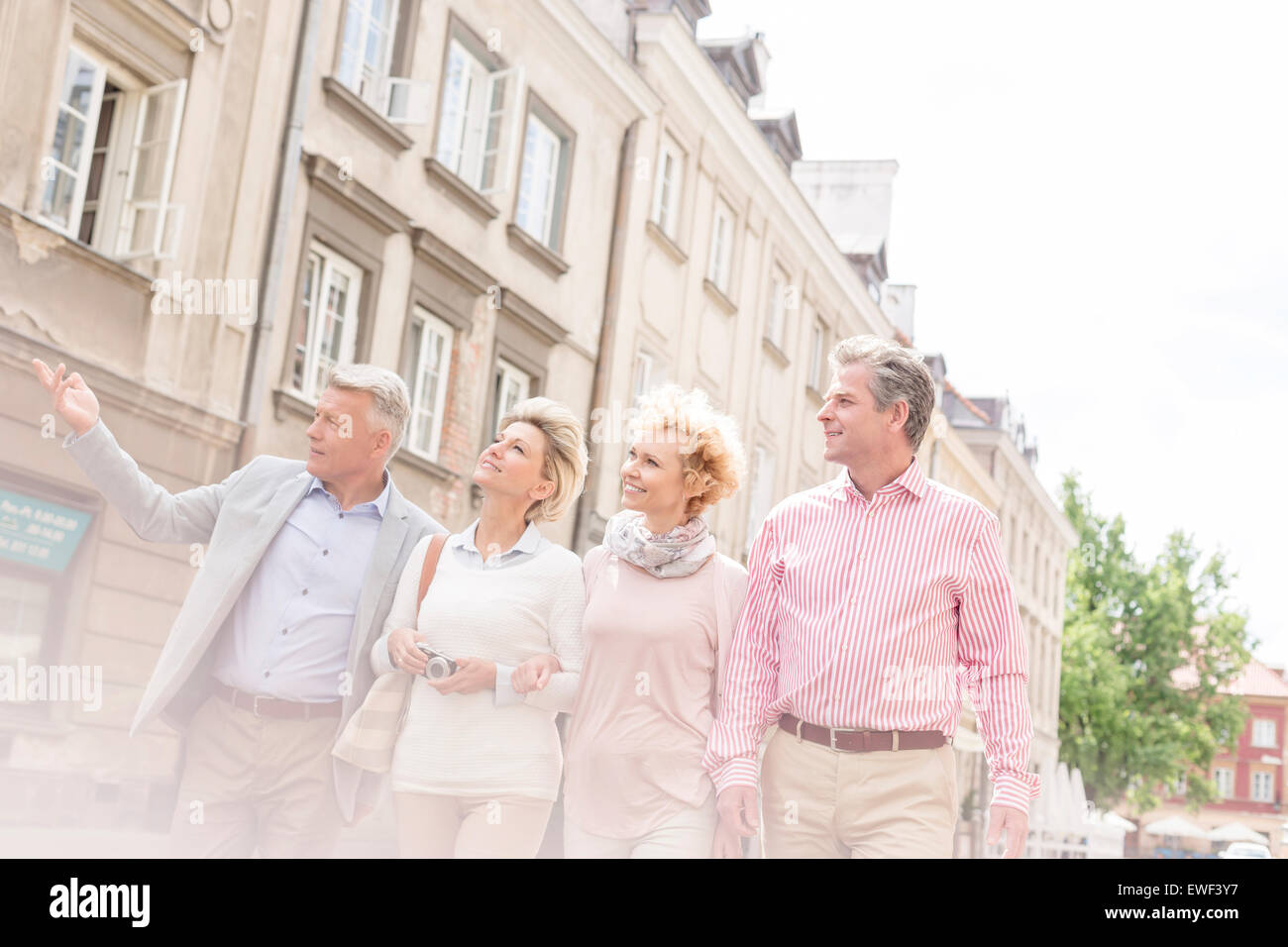 Middle-aged man showing something to friends while walking in city - Stock Image