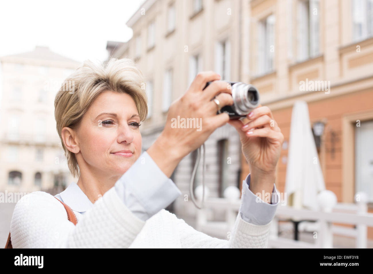 Woman photographing through digital camera in city - Stock Image