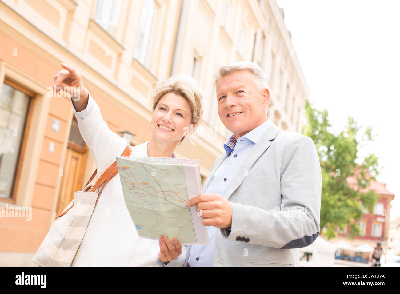 Middle-aged woman showing something to man with road map in city - Stock Image