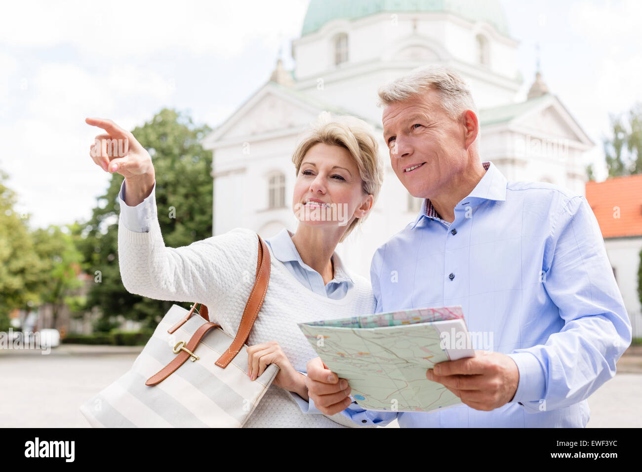 Middle-aged woman showing something to man holding map outdoors - Stock Image