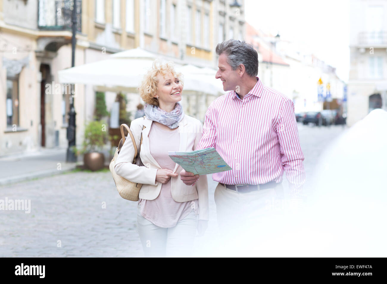 Smiling middle-aged couple with map looking at each other while walking in city - Stock Image
