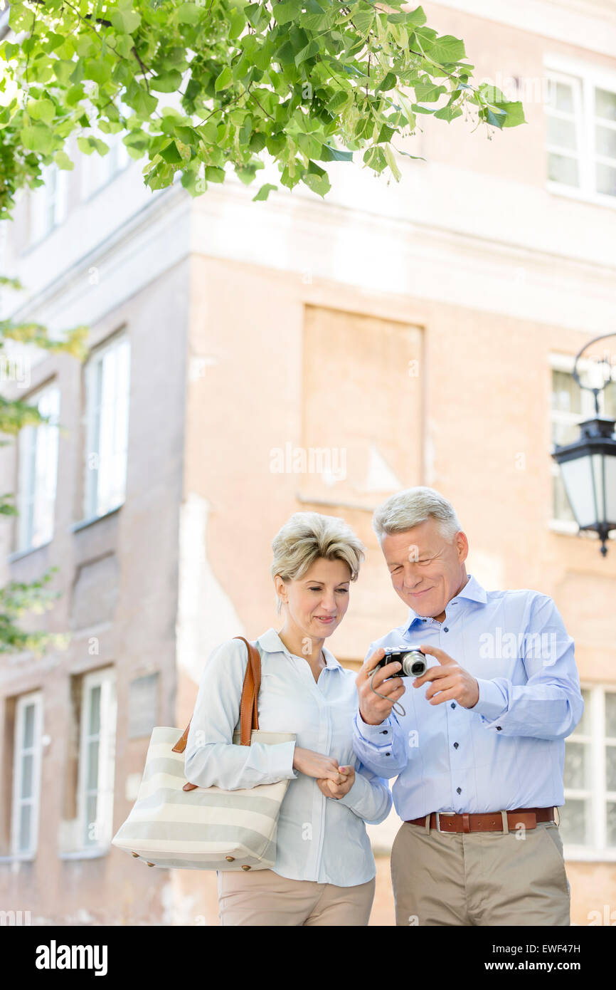 Middle-aged couple reviewing photos on digital camera outside building - Stock Image