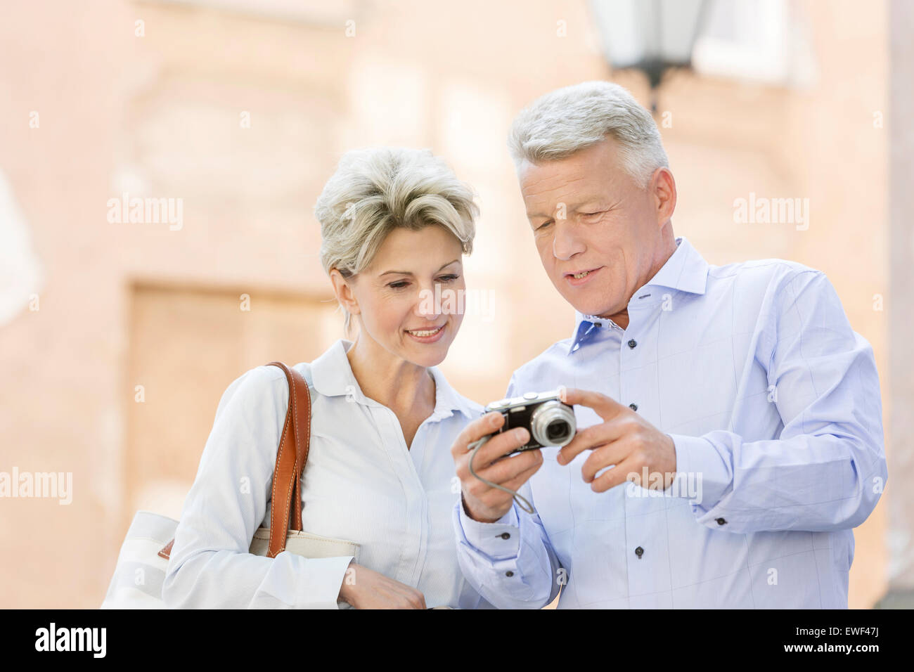 Smiling middle-aged couple reviewing photos on digital camera outdoors - Stock Image