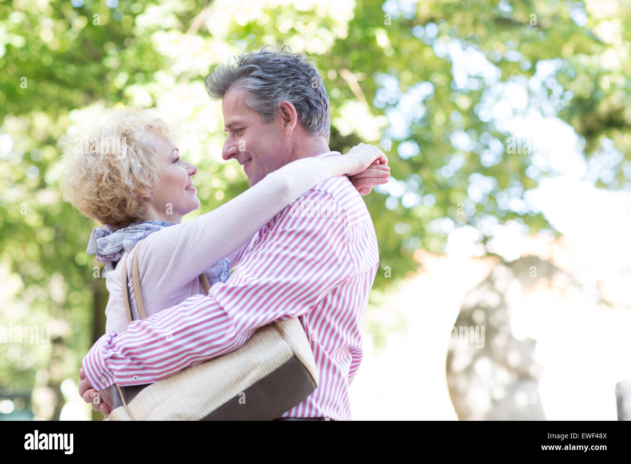 Side view of middle-aged couple embracing while looking at each other in park - Stock Image