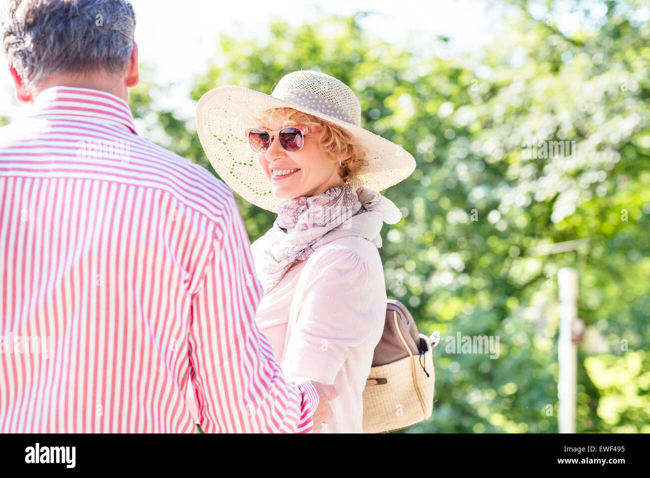 Happy middle-aged woman with man in park Stock Photo