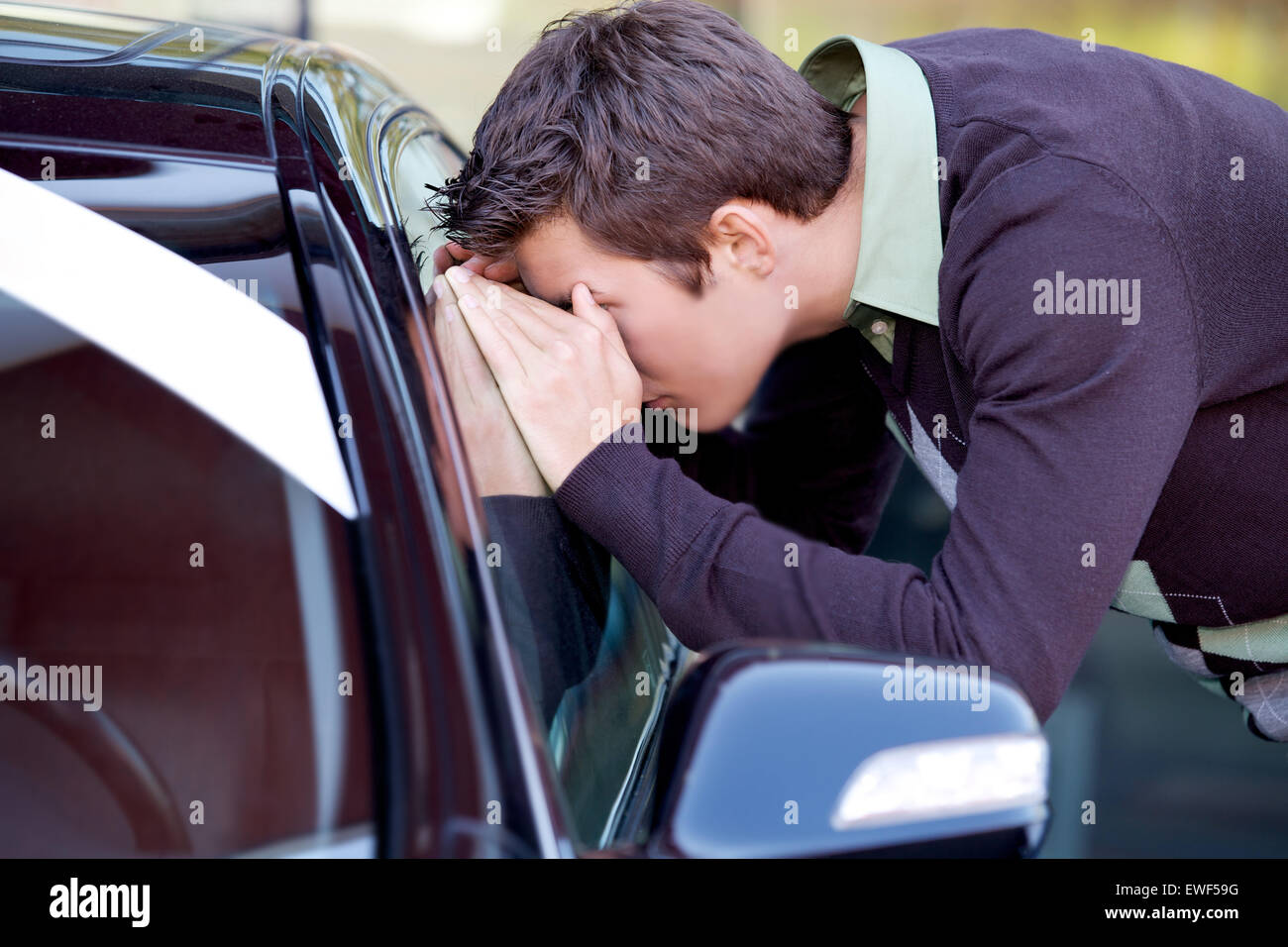 Young man looking at new car - Stock Image