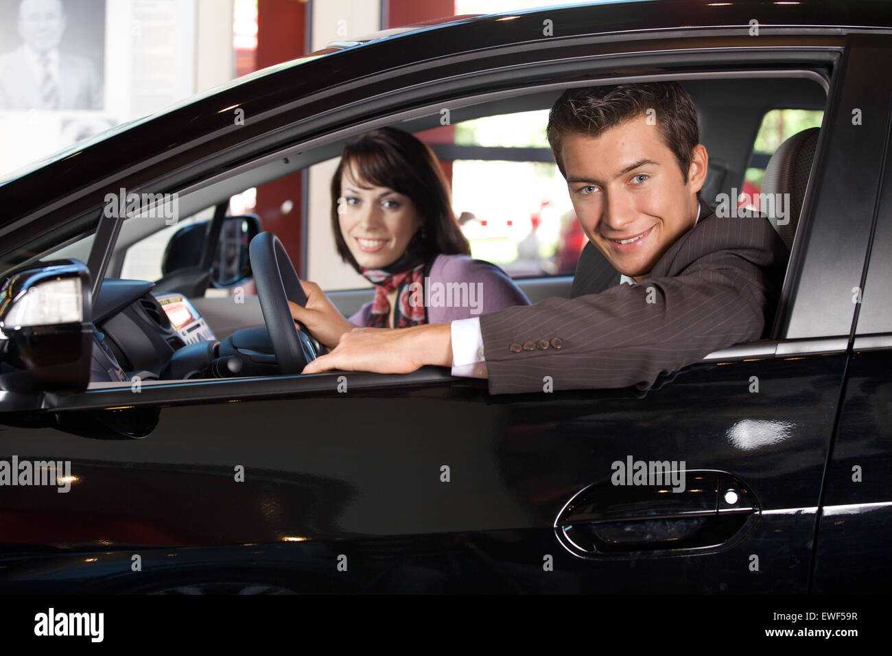 Portrait of young couple sitting in a new car at showroom - Stock Image