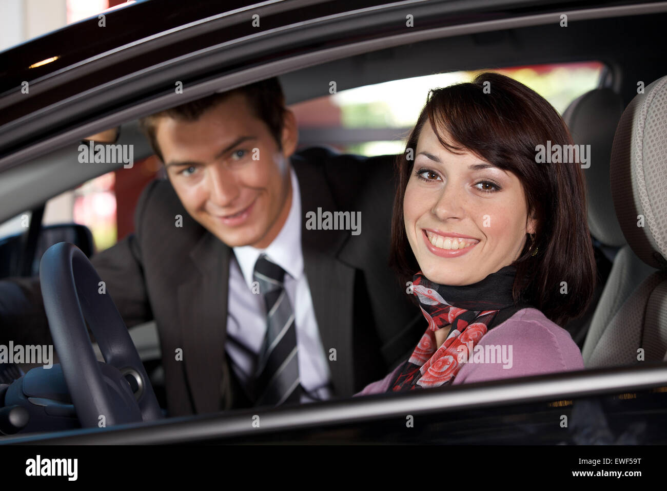 Portrait of young couple sitting in a new car at showroom Stock Photo