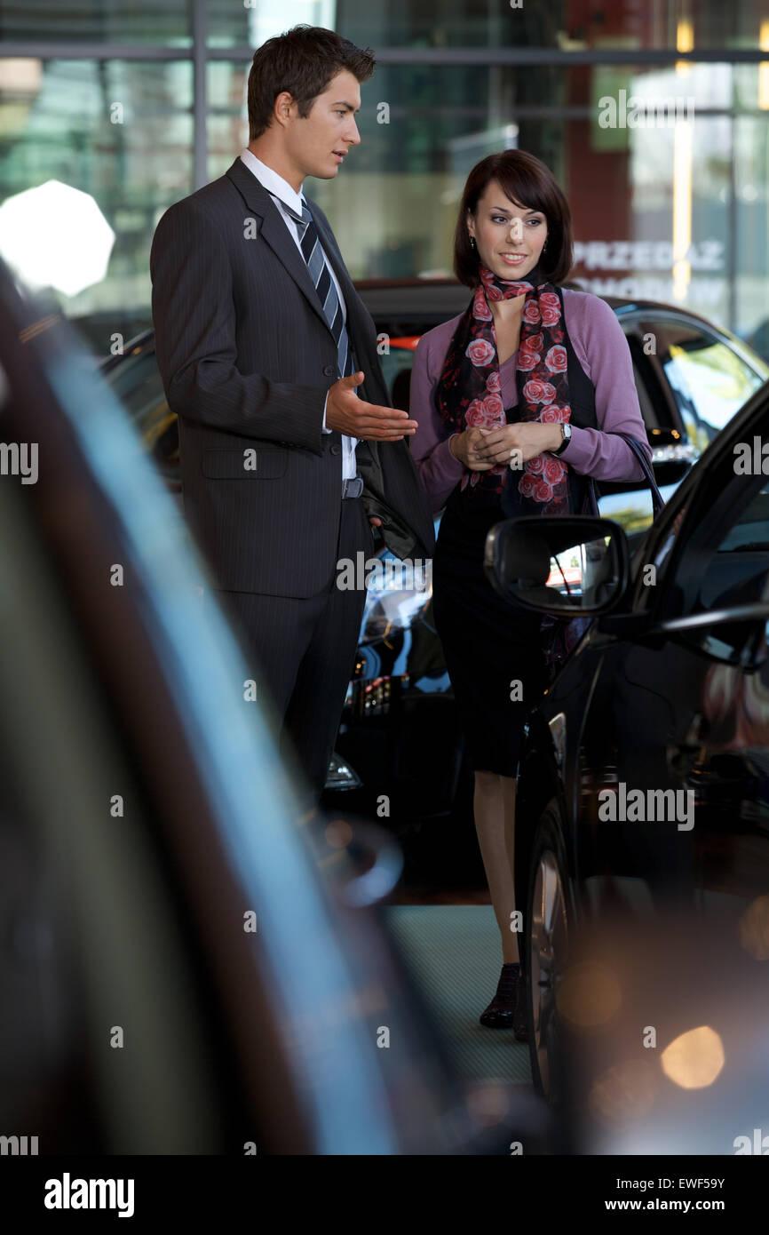 Car salesman explaining car features to customer - Stock Image
