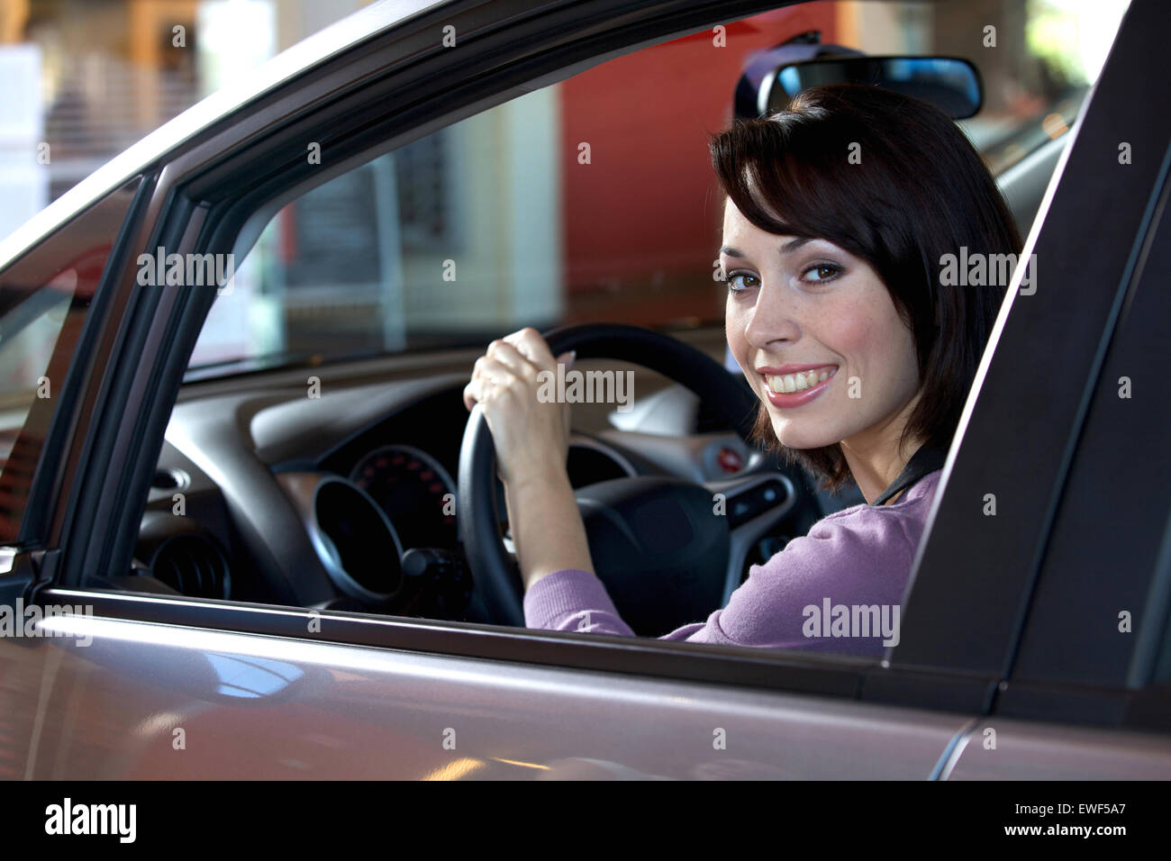 Portrait of young woman sitting in driver's seat at car dealership - Stock Image