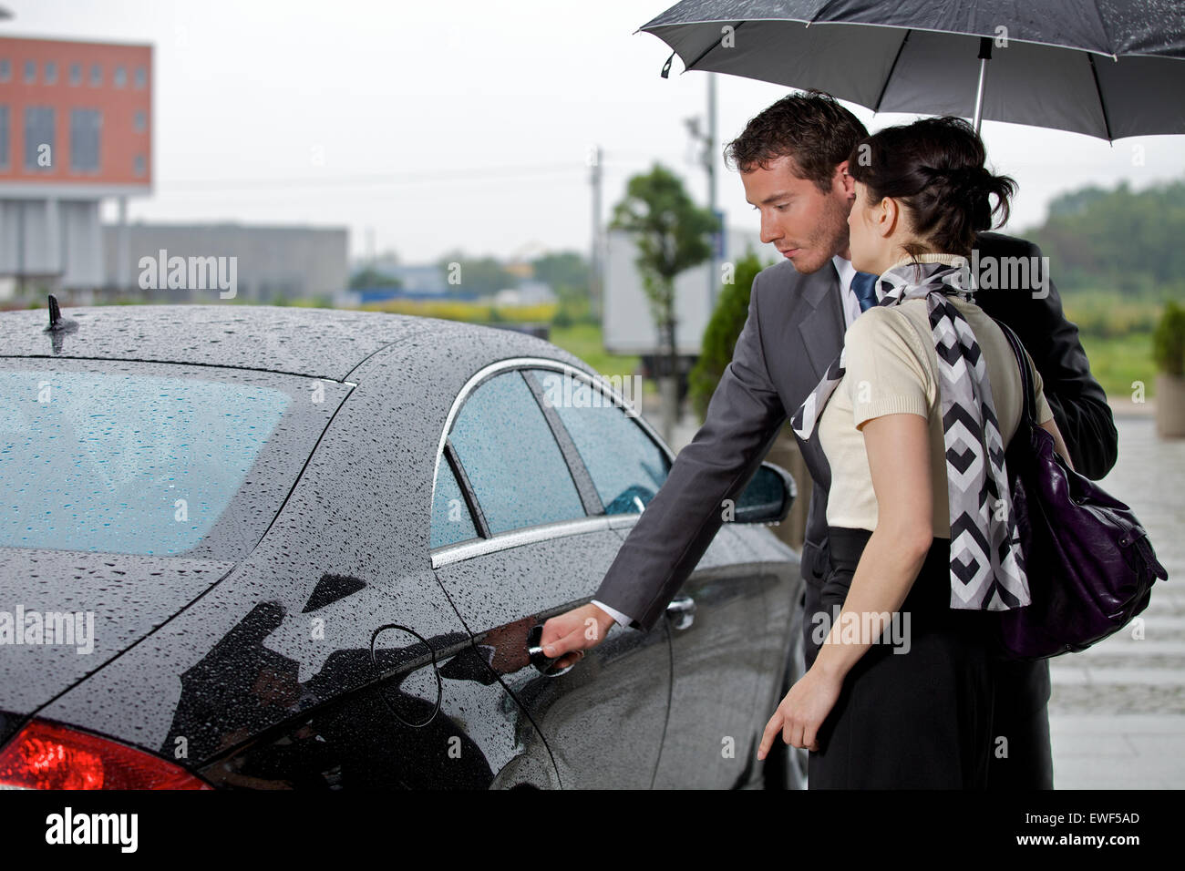 Young man opening door of car for woman - Stock Image