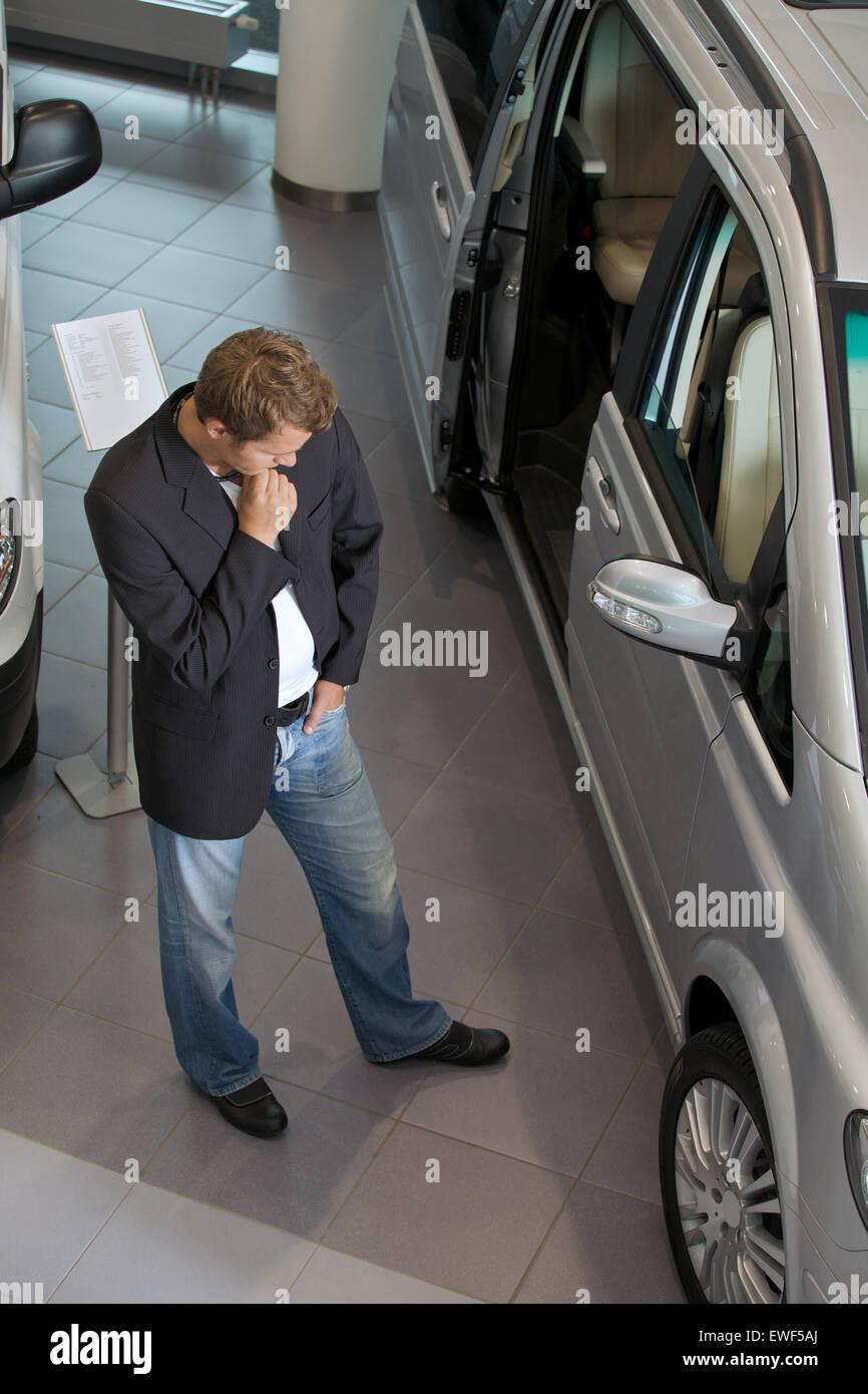 Young man examining new car at showroom - Stock Image