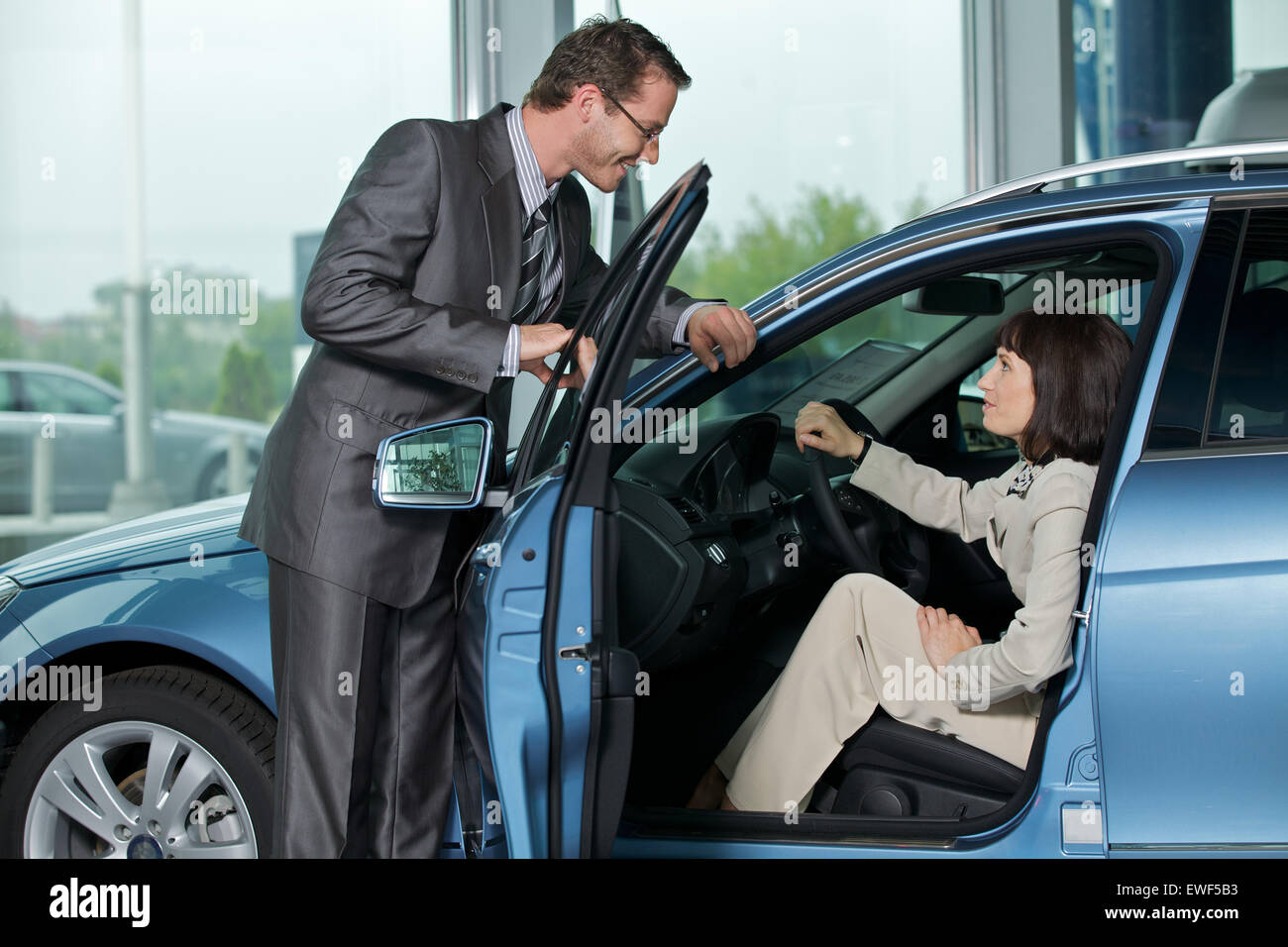 Car salesperson explaining car features to customer - Stock Image