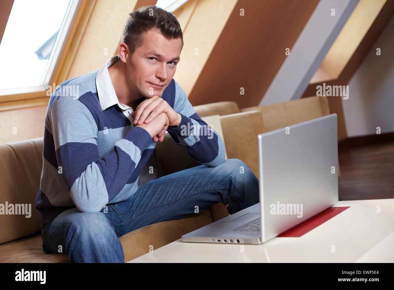 Man sitting on sofa - Stock Image