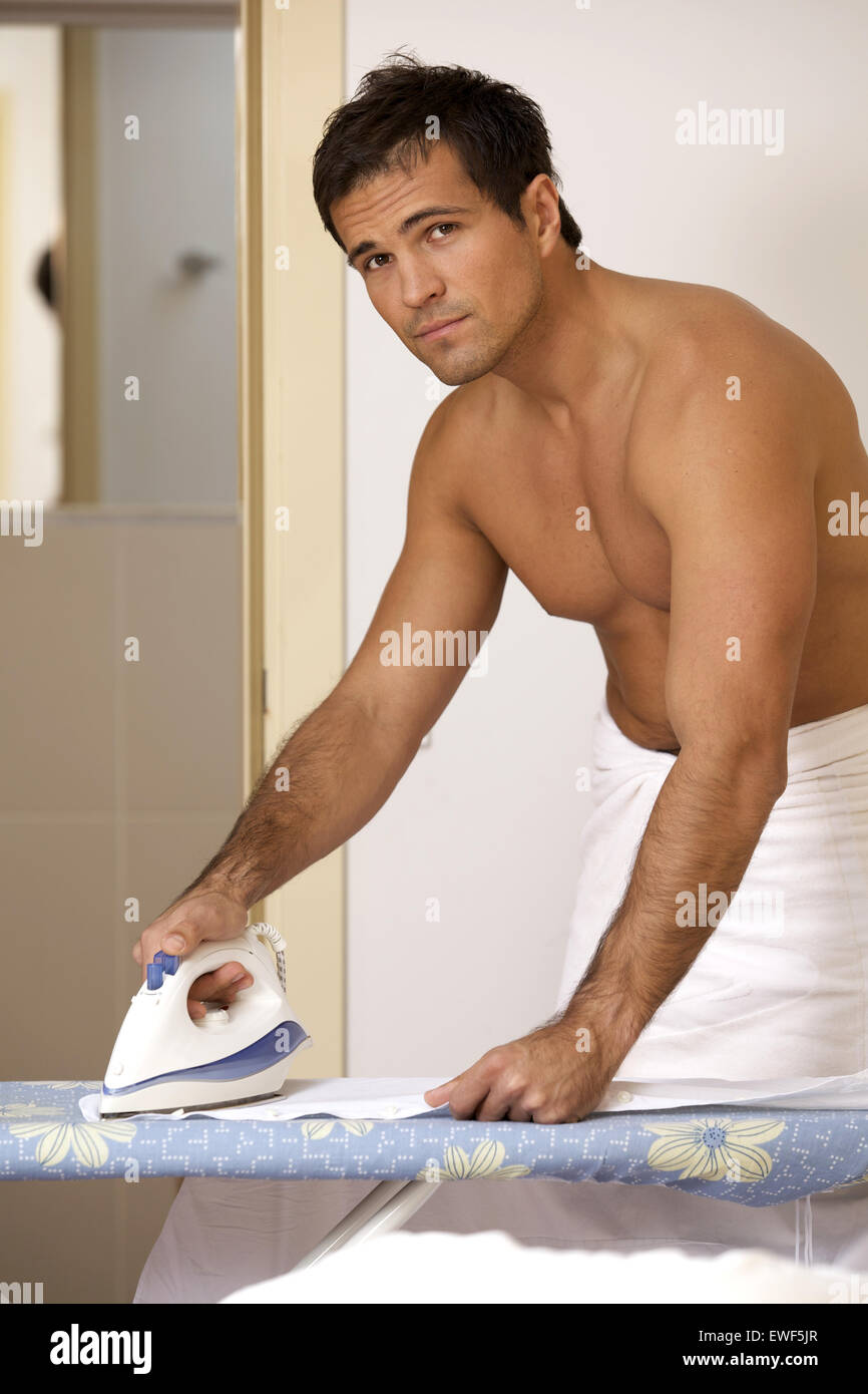 Portrait of man in towel ironing clothes on a stand - Stock Image