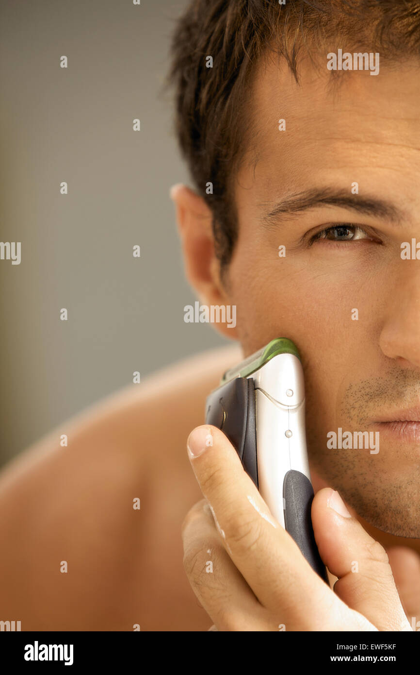 Reflection of young man in mirror shaving with electric shaver - Stock Image
