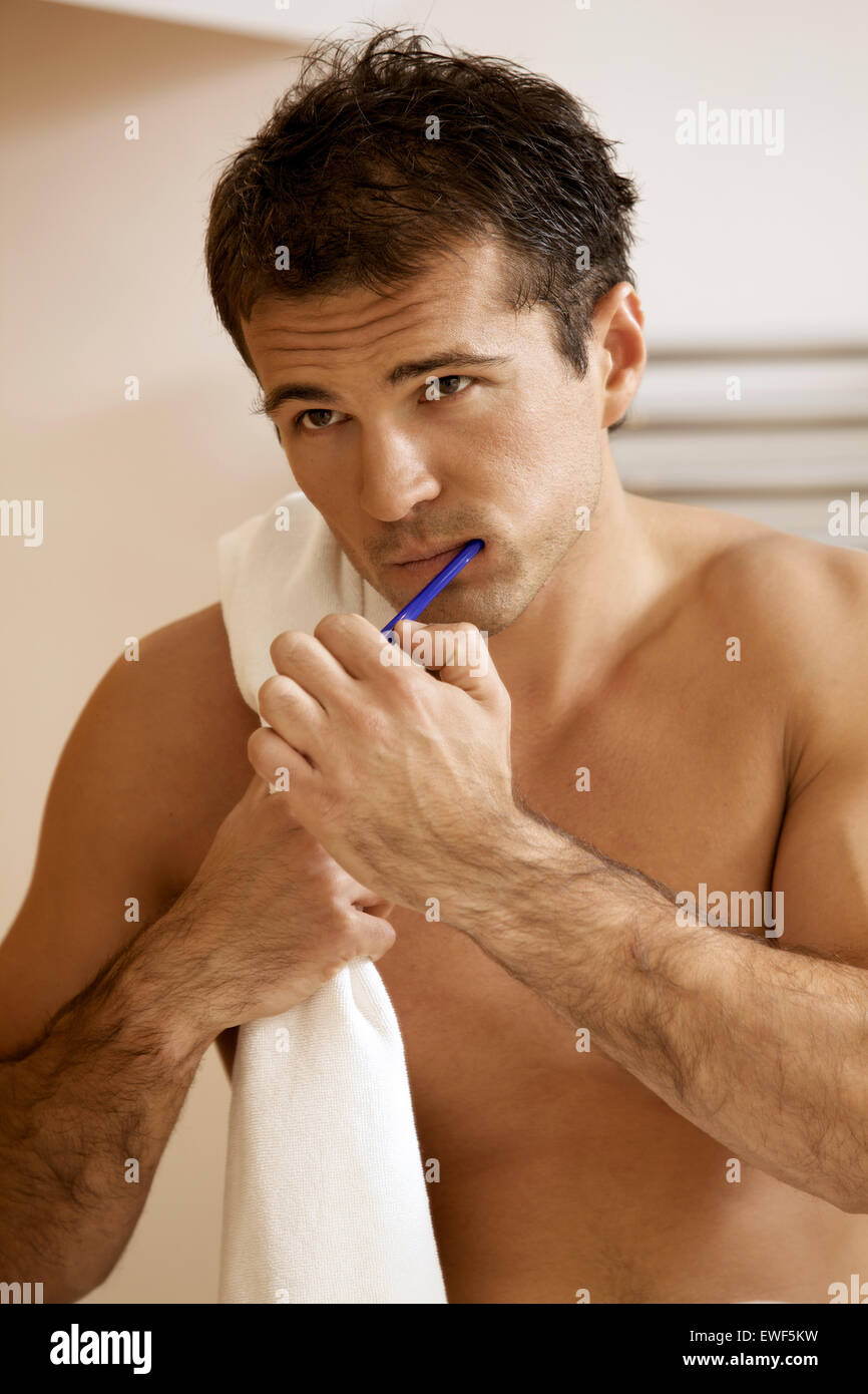 Reflection in a bathroom mirror of a young man brushing his teeth Stock Photo