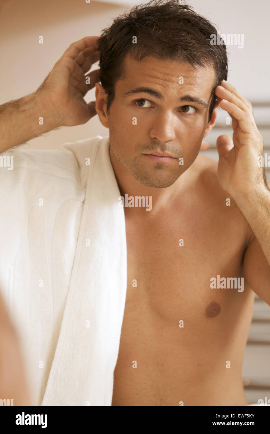 Young man looking into mirror - Stock Image