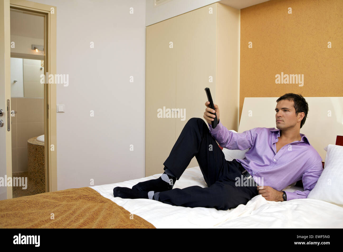 Man on bed with remote control - Stock Image